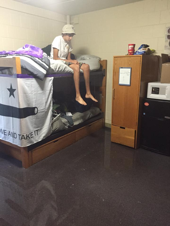 Weinberg Freshman  Nabeel Muscatwalla looks down from his lofted bed at the half an inch of standing water on his bedroom floor in PARC.