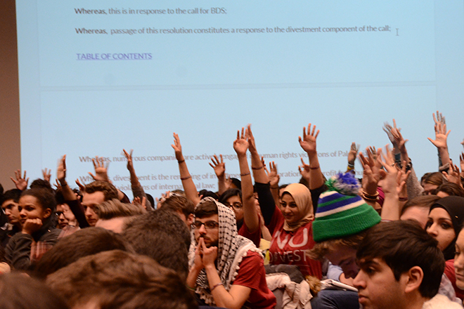 Students who support NU Divest raise their hands to speak during the debates at the Feb. 19, 2015 ASG meeting.